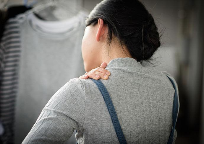 肩を押さえている女性