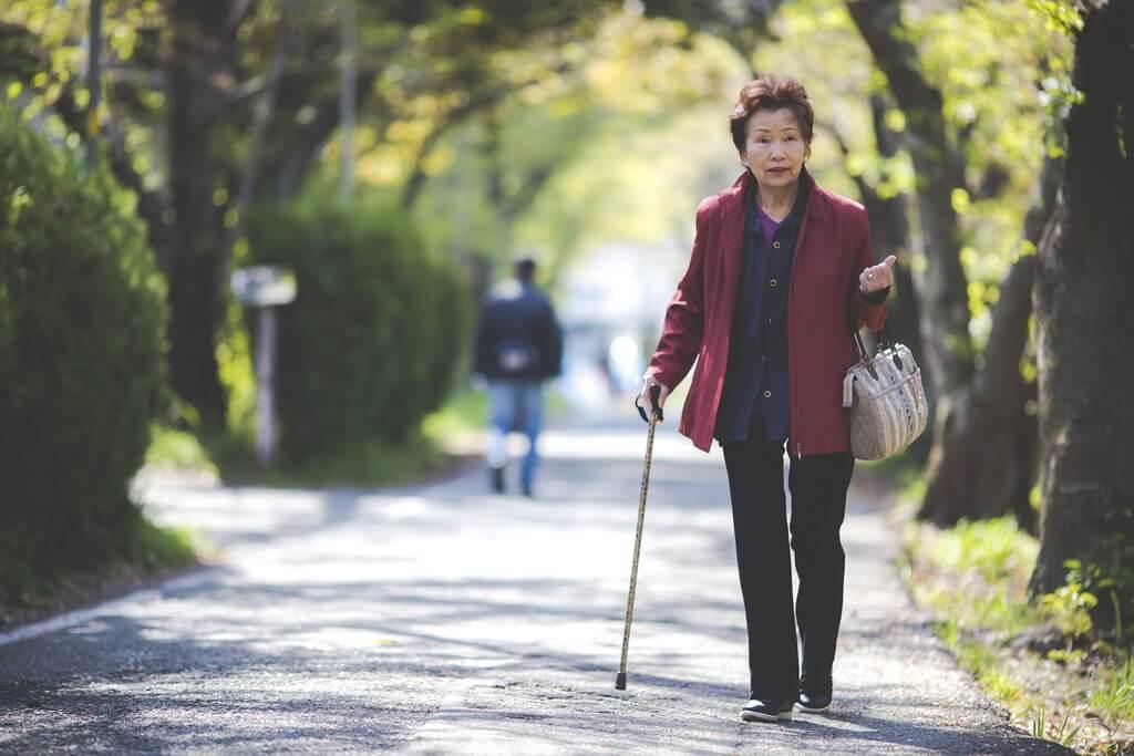杖をついた女性が歩いている様子